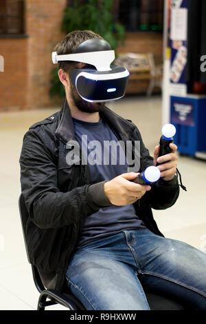 Dans l'homme casque VR qui profitant de jeu. La réalité virtuelle. l'homme à casque VR avec joysticks