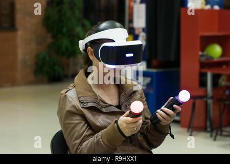 En fille casque VR qui profitant de jeu. La réalité virtuelle. L'adolescent au casque VR avec joysticks