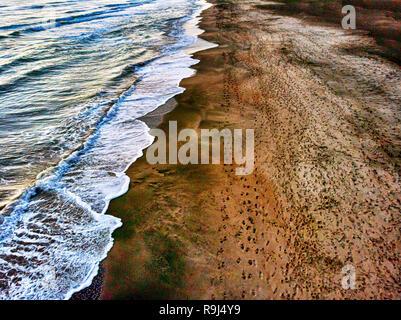 Vue aérienne d'un magnifique littoral et contre-courant avec des traces sur le sable
