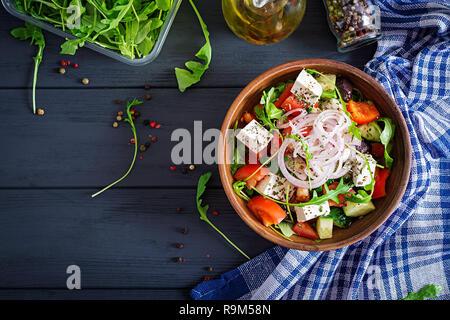 Salade grecque avec de la tomate, concombre, oignon rouge, basilic, fromage feta, olives noires et herbes italiennes. Vue d'en haut