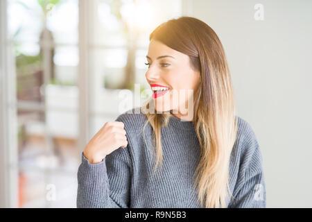 Belle Jeune femme portant le chandail d'hiver à la maison à la voiture à l'autre avec le sourire sur le visage, expression naturelle. Rire confiant.