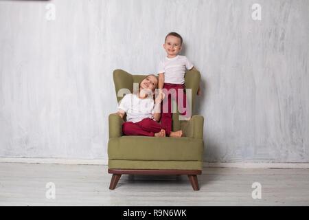 Garçon et fille sont frère et sœur s'asseoir sur un canapé dans la chambre verte Banque D'Images