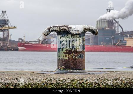 IJmuiden (Pays-Bas), le 22 décembre 2018: l'acier à un bollard Amarrage quai en béton, avec l'aciérie Tata et le Canal de la mer du Nord dans le background Banque D'Images