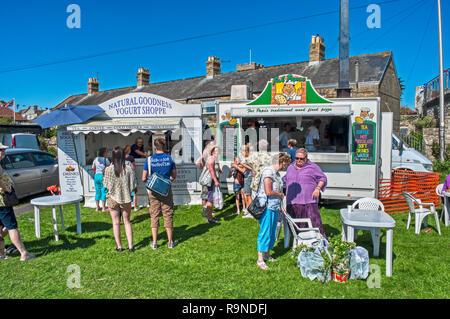 Kiosques alimentaires avec les personnes au service de clients et à l'extérieur à l'événement en plein air, à l'île de Wight, Royaume-Uni Banque D'Images