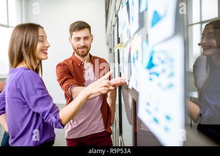 Jeune homme et femme vêtue de désinvolture travailler avec quelques statistiques sur le mur de verre dans le bureau