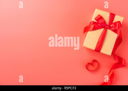 Boîte-cadeau avec ruban rouge dans la couleur tendance de 2019 fond corail vivant, concept de la Saint Valentin, anniversaire, fête des mères, l'espace de copie, vue du dessus. Banque D'Images