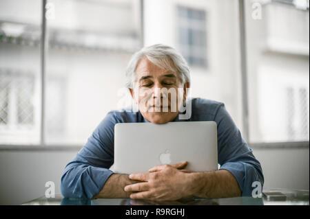 Contenu mature businessman hugging son ordinateur portable. Banque D'Images