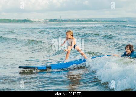 Petit garçon surf on tropical beach. Enfant sur planche de surf sur les vagues de l'océan. Sports d'eau Active pour les enfants. Piscine pour enfants avec surf. Leçon de surf pour les enfants Banque D'Images