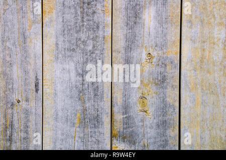 Planche en bois patiné avec la texture des restes de peinture jaune. Close-up. Banque D'Images