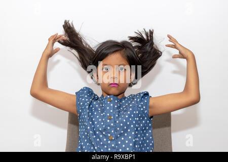 Petite fille jouant avec ses cheveux Banque D'Images