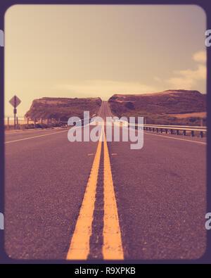 Lignes de démarcation routière jaune sur une route le long de la côte californienne avec effet filtre retro vintage Banque D'Images