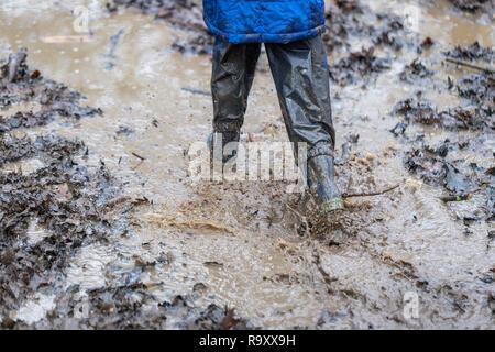 Jeune enfant jouant dans une flaque de boue Banque D'Images