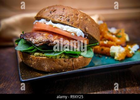 Sandwich aux champignons portobello au fromage de chèvre et pesto au côté de frites de patates douces Grec Banque D'Images