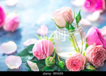 Bouteilles en verre avec pivoine rose roses sur un fond clair avec l'exemplaire de l'espace. Coupe féminine de pétales et de fleurs dans des tons pastel Banque D'Images