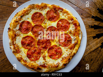 Toute ronde pizza au pepperoni, servi sur une assiette assise sur une table à grain de bois Banque D'Images
