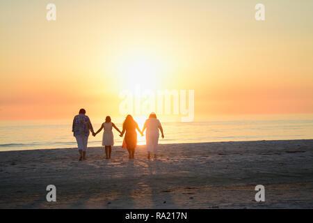 Heureux famille aimante tenant la main et embrassant tout en faisant face à la lumineuse jaune orange coucher de soleil sur l'océan à l'horizon sur les plages de Floride Banque D'Images