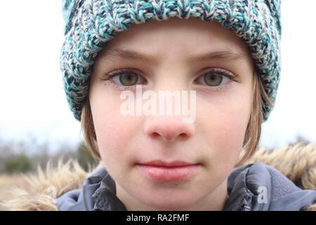 Portrait d'une fille aux yeux vert intense portant une casquette dans le froid de l'hiver Banque D'Images