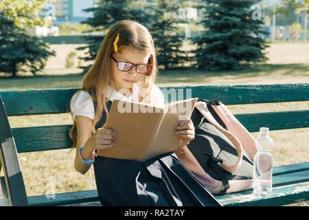 Petite fille intelligente dans les verres avec un sac à dos pour l'école lecture livre assis sur un banc dans le parc. Banque D'Images
