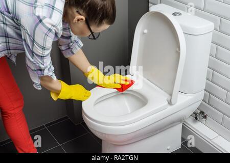 Nettoyage de la maison. Nettoyage des toilettes femme, femme dans des vêtements décontractés avec un détergent et une débarbouillette à la maison dans la salle de bains. Banque D'Images