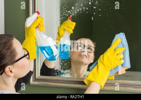 Service de nettoyage professionnel. Femme dans les gants en caoutchouc faisant le nettoyage dans la salle de bain, nettoie le miroir avec chiffon et un détergent. Banque D'Images