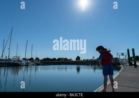 Petit garçon à la recherche vers le bas en rouge veste de pêche pier de marina sur calme ensoleillé matin silhouetté par le soleil du matin Banque D'Images