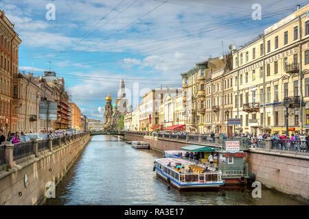 Saint Petersburg, Russie - 8 juin 2018 - grand groupe de balades touristiques à proximité d'un canal avec une immense église en arrière-plan et des bâtiments traditionnels en Banque D'Images
