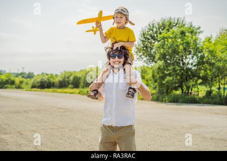 Happy father and son Playing with toy airplane contre l'ancienne piste d'arrière-plan. Concept de voyager avec des enfants Banque D'Images