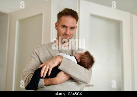 Jeune père de famille est titulaire d'enfant, 4 semaines, sur bras, Bade-Wurtemberg, Allemagne Banque D'Images