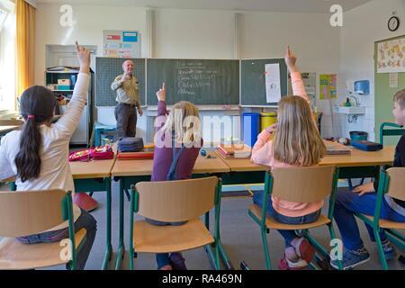Les élèves à l'école primaire avec des mains en classe, Basse-Saxe, Allemagne Banque D'Images