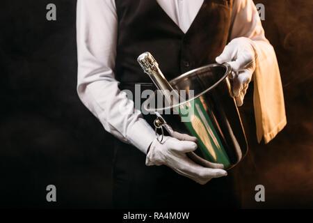 Portrait of waiter holding bouteille d'alcool dans le seau à champagne sur noir