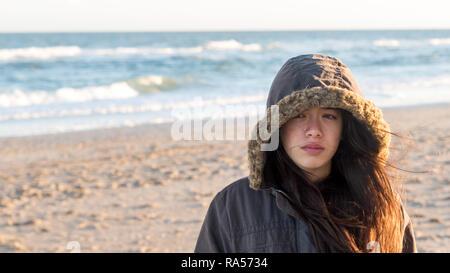 Les jeunes Américains d'origine à la North Carolina Beach en hiver en parka à capuchon Banque D'Images