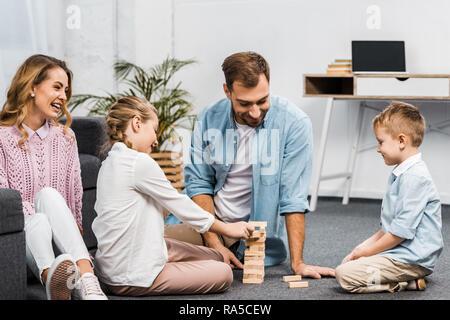 Deux heureux parents jouant tour en bois blocs de jeu avec la fille et le fils sur le plancher dans la salle de séjour Banque D'Images