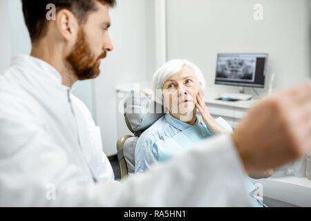 Femme aîné inquiet pendant la consultation avec beau dentiste montrant une radiographie panoramique dans le cabinet dentaire