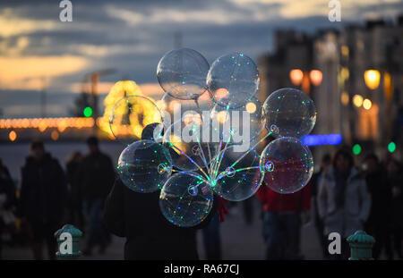 Brighton UK 1er janvier 2019 - Un homme porte des ballons le long front de mer de Brighton au coucher du soleil après une belle après-midi sur la côte sud de Bretagne Crédit: Simon Dack/Alamy Live News Banque D'Images