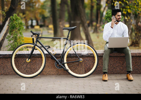 Happy young indian man en shirt talking on mobile phone while sitting with laptop computer outdoors with bicycle