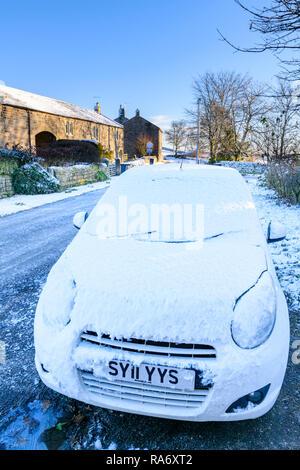 Close-up of voiture garée sur la rue main glacée de petit village rural pittoresque, sur le froid, la neige journée d'hiver - Timble, North Yorkshire, England, UK Banque D'Images