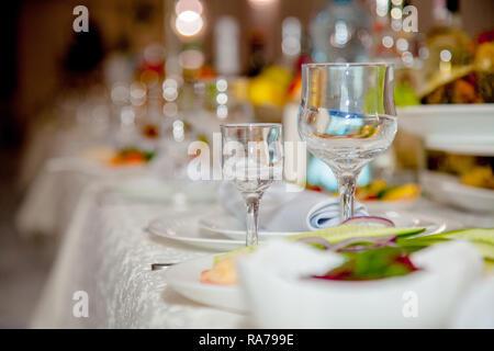 La table de fête avec des verres sur une table. Verres vides se tiennent près de plaques et fourchettes sur table de banquet décorée de tablewear. Servi de fête Banque D'Images