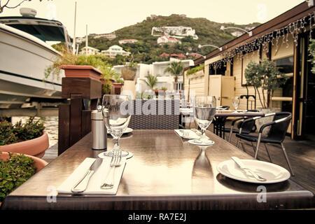 Table et chaises sur la terrasse du restaurant sur fond naturel à Philipsburg, Sint Maarten. Verres et couverts. Repas et boissons à l'extérieur. Les vacances d'été et les jours fériés. Profiter de la vie. Banque D'Images