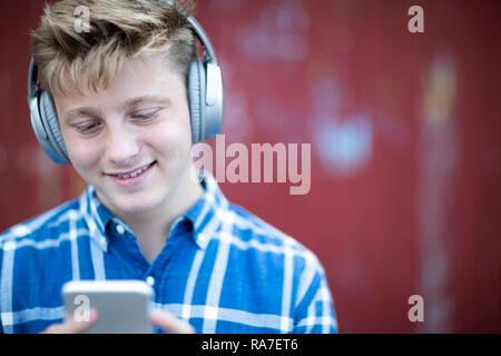 Teenage Boy portant un casque sans fil et d'écouter de la musique en milieu urbain Banque D'Images