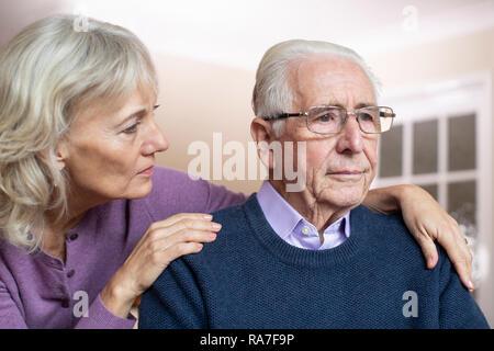 Confused Senior homme souffrant de dépression et de la démence d'être réconforté par femme Banque D'Images