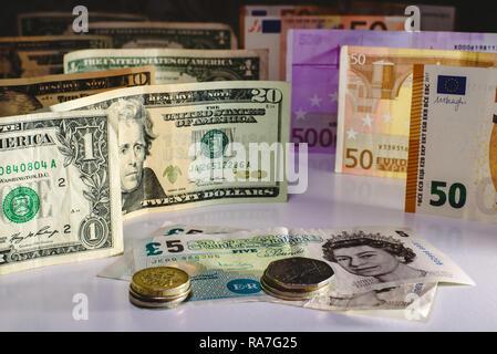 Livre sterling et de l'anglais bill acculés par des pièces d'euros et de dollars. Banque D'Images