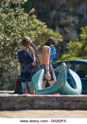 Un garçon d'âge de l'adolescence à l'aide d'un smartphone, et une fille avec son visage de séchage serviette bleue; la marche loin après un bain rafraîchissant à l'aménagement de plage, Yamba, Australie. Banque D'Images