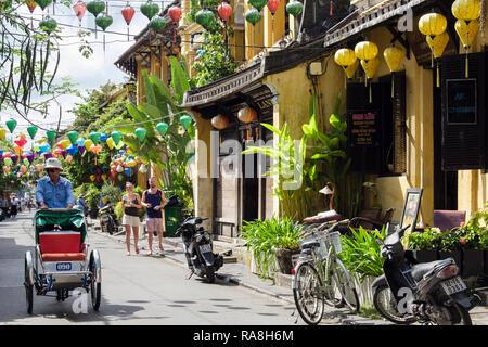 Rue étroite avec des lanternes suspendues dans vieux quartier historique avec le cyclo-pousse. Hoi An, Quang Nam Province, Vietnam, Asie Banque D'Images