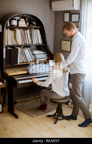 Jeune couple aimant jouer du piano dans la chambre à la maison Banque D'Images