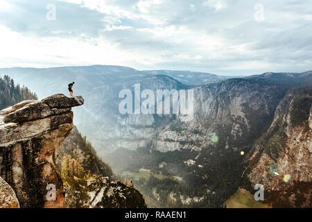 L'intrépide randonneur est debout sur la roche en surplomb à Glacier Point profiter de la vue sur la vallée Yosemite, Yosemite National Park, California, USA Banque D'Images