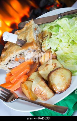 Un pub anglais plat principal servi avec pie Jeu de chou râpé, les carottes, les pommes de terre de la Baton et sauce sauce. Banque D'Images