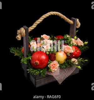 Cadeau original sous la forme d'une boîte en bois remplis de fleurs et de fruits différents sur un fond noir Banque D'Images