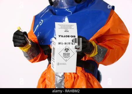 Pompier portant un vêtement de protection pour le contrôle des maladies tenant un récipient de collecte d'échantillons, pompier professionnel Banque D'Images
