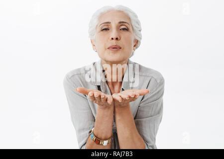 Taille plan sur charmant aux cheveux gris femme âgée en flexion vers la caméra holding shirt palms près de lèvres plissées de l'envoi à l'air de soufflage de l'appareil photo kiss mwah à mari toujours l'aimer passionnément Banque D'Images