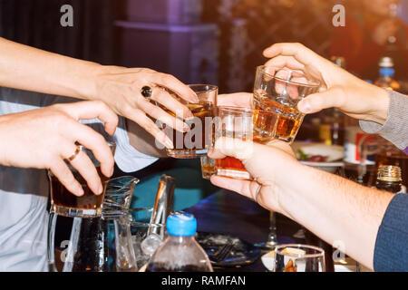 Des gens qui ont des lunettes un toast. Groupe d'amis toasting et applaudir les verres, boire au bar. Les gens avec l'interlocuteur des cocktails. Anniversaire, fête concept. Banque D'Images